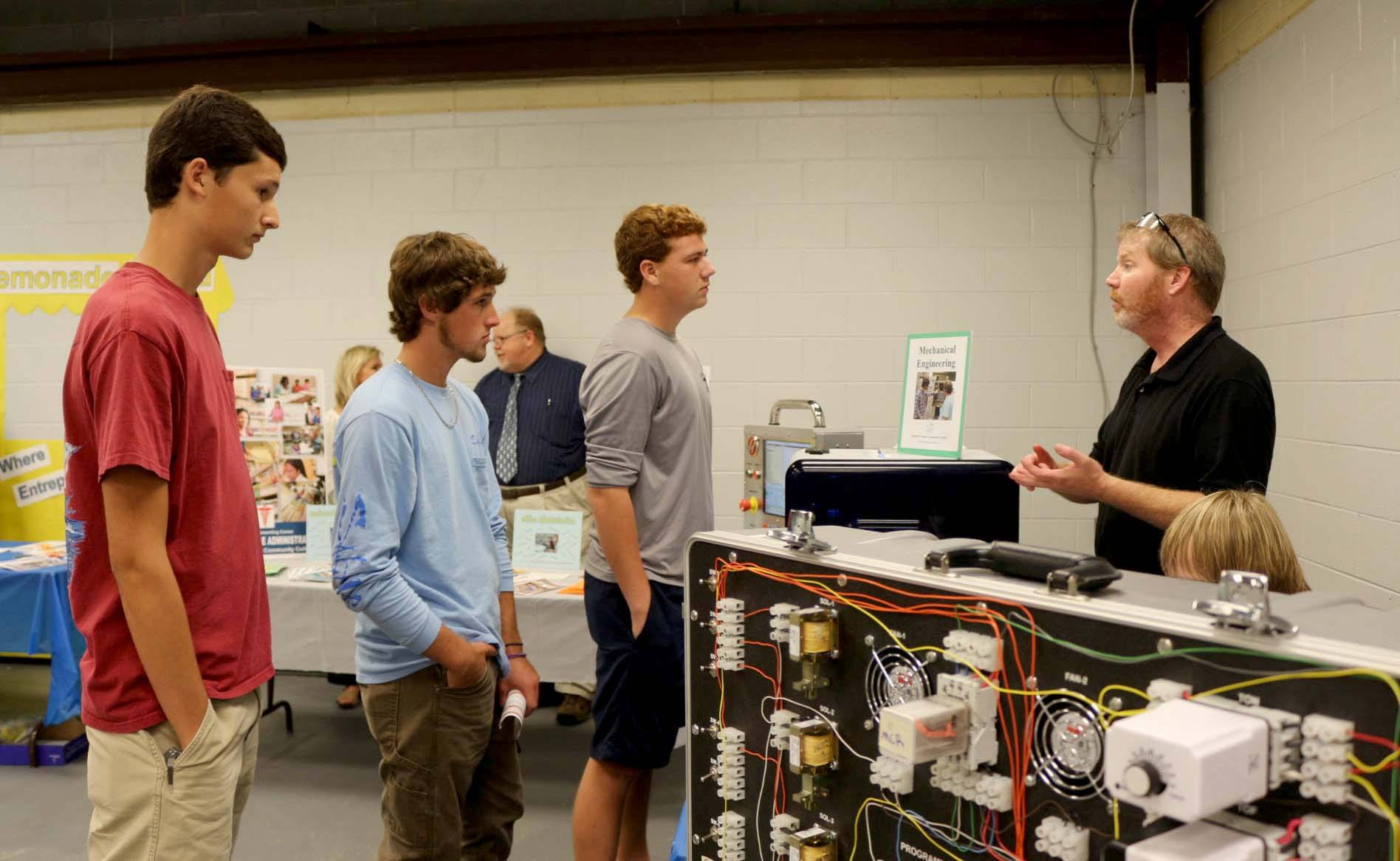 Three students talk to Mechanical Engineering Instructor Matthew Lincoln.