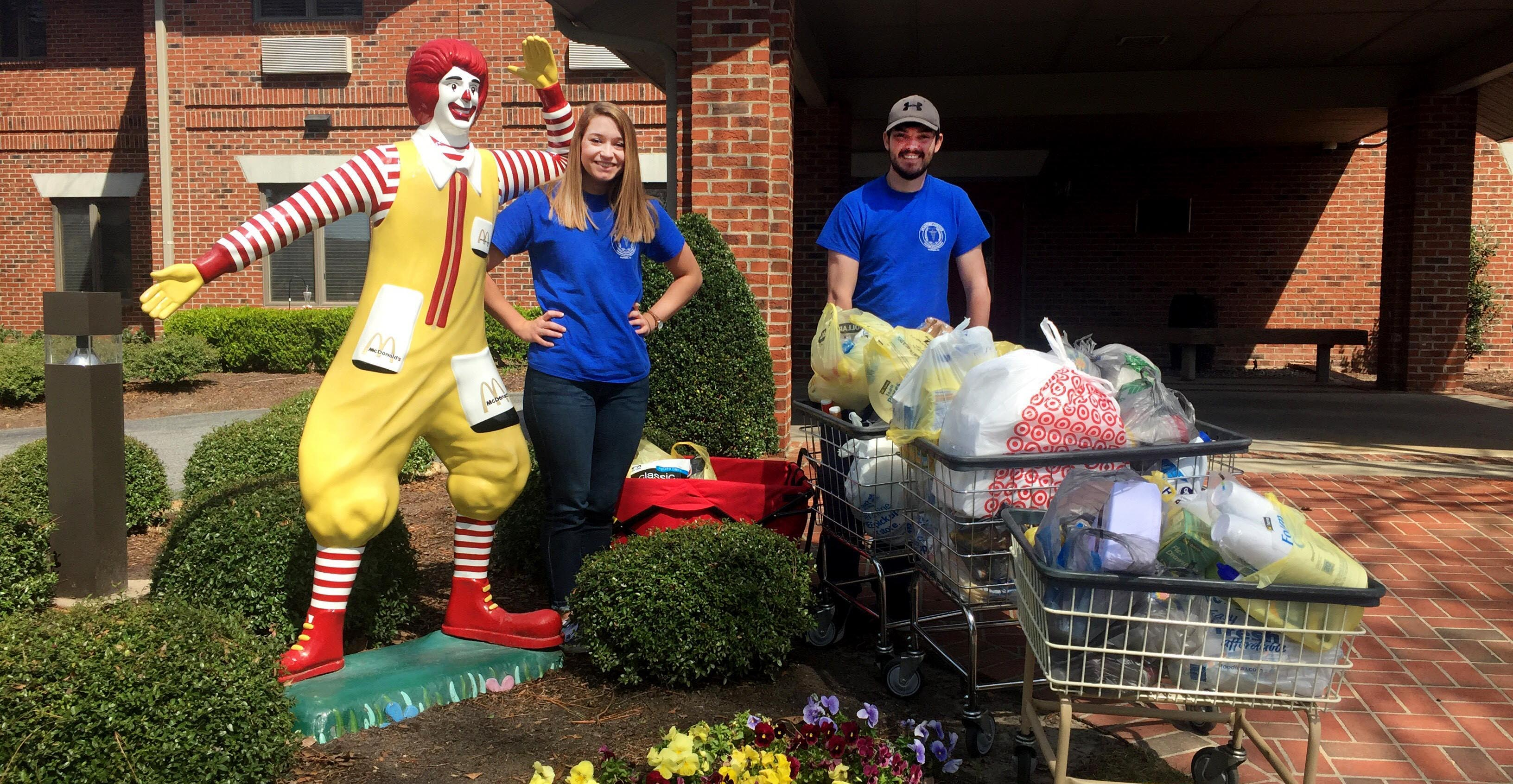 Two students stand with donations and a statue of Ronald McDonald.